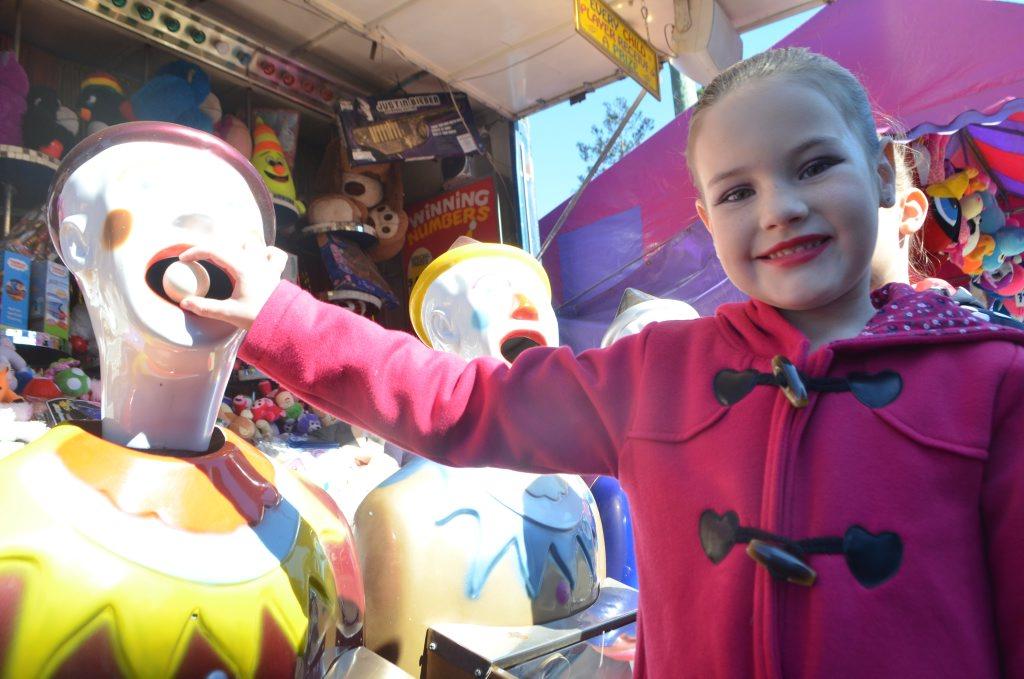FAMILY FUN: Chloe George tries her luck on a sideshow alley game. Photo Ali Kuchel / Gatton Star