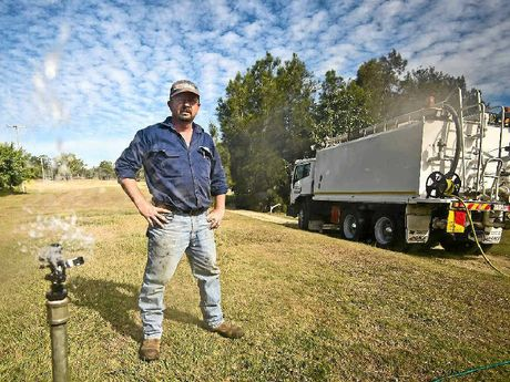 DROUGHT STRICKEN: Greens director Craig Topfer stands on the Boyne Island golf course which is lifeless due to council's decision to terminated water supply used to sustain the green. A water truck has been brought in to keep the green alive.