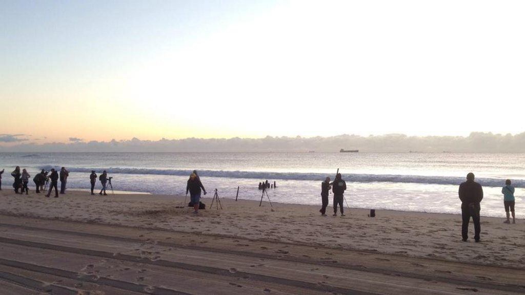 Photographers gather at Dicky Beach for one last sunrise photoshoot.