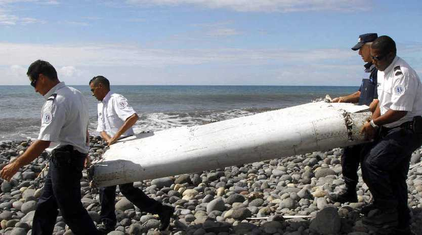 NEW HOPE: Officers carrying pieces of debris from an unidentified aircraft apparently washed ashore in Saint-Andre de la Reunion, eastern La Reunion island, France, late last week. A Malaysian government team has been dispatched to Reunion in the Indian Ocean, where newly found aircraft wreckage awakened speculation over flight MH370.