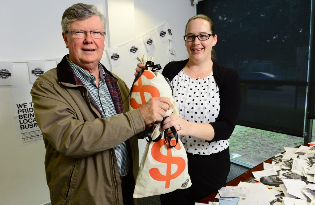 HAPPY SHOPPER: Last year's City Pride major prize winner Bernard Atkins receives his $5500 spending money from QT Features & Special Publications Manager Rebecca Carter