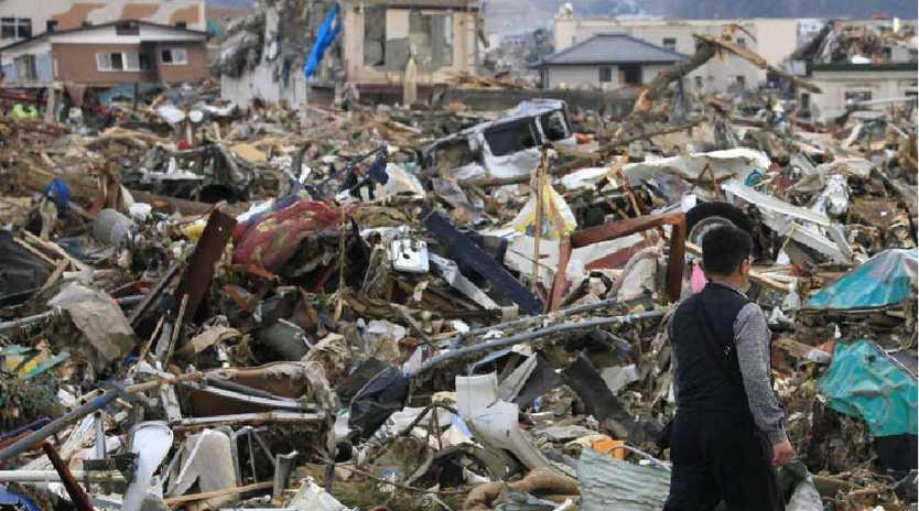 HORROR SCENE: A man walks through debris in tsunami-devastated city of Rikuzentakata in northern Japan in 2011.