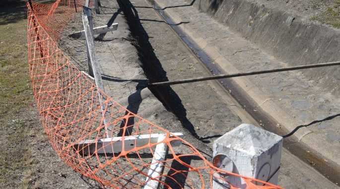 FEELING DRAINED: This drain on Edward Street drain has had the fencing half knocked down for about 12 months. Council workers have put up bright orange netting covering it. Photo: Max Fleet / NewsMail