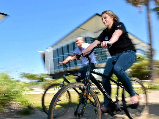TAKING A SPIN: Youi employees (from left) Dion Locke and Mary Maclean use company bikes around the lake outside the Youi offices on Lake Kawana Boulevard.