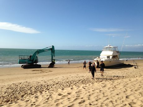 An excavator arrives on Torquay Beach to start the salvage operation of a beached cruiser.