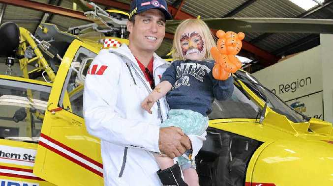 PROTECTION: Australian ironman and dual Olympian Ky Hurst, the Westpac Rescue Helicopter Schools Program ambassador, with son Koa, 2, at the service's Open Day.