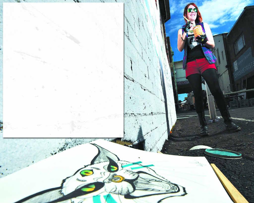 WALL TRANSFORMED: Solo artist Kate Hallen, of Lismore, gets stuck into the live street art revamping of Larkin Lane.