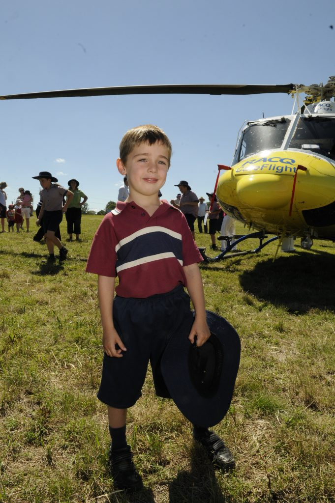 Patrick O'Sullivan with the RACQ CareFlight helicopter on the oval of Mary MacKillop Catholic School.