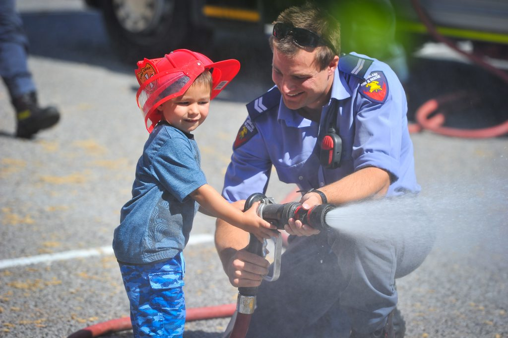 Hugo Butler, 3, has a go at using the water hose.