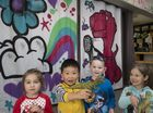Mirambeena Children's Centre students (from left) Grace Zwoerner, Josh Zhang, William Utley and Lydia Shirtcliff are excited about their graffiti curtains painted by Kontraband director Ian McCallum.