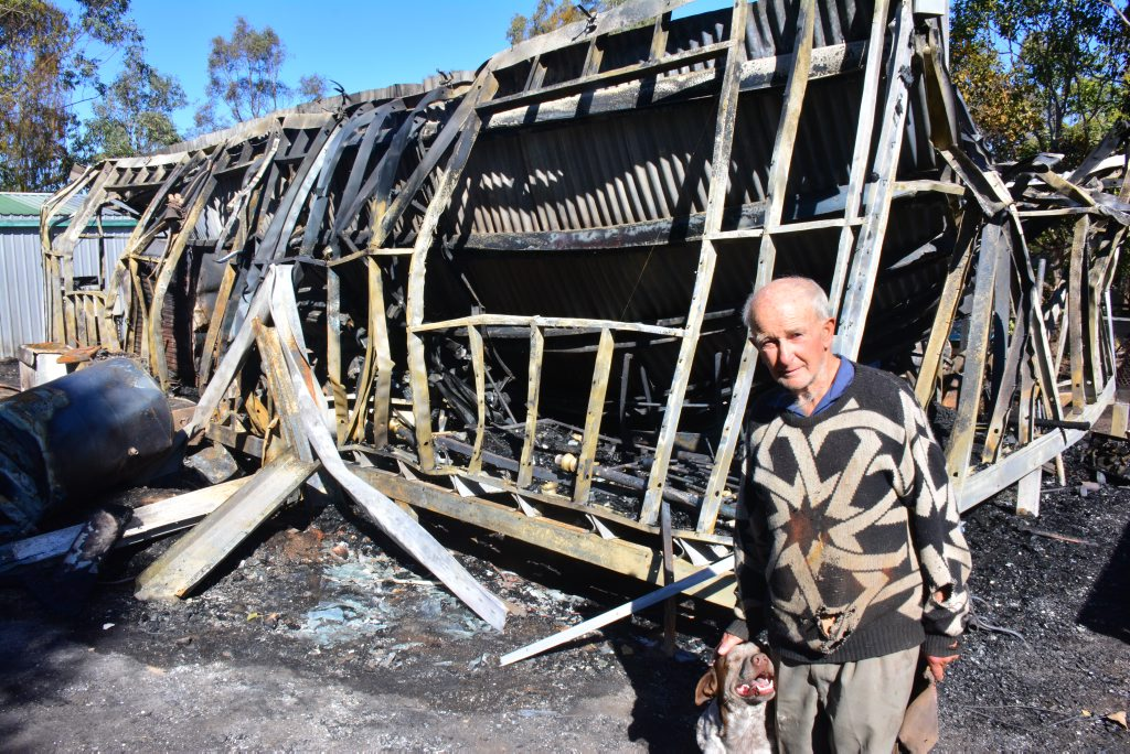 Roy Morrison and his dog Whitey with what is left of their home.