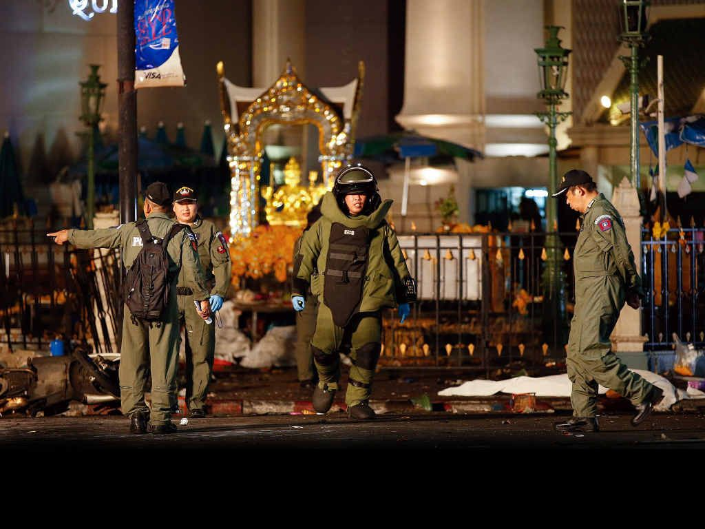 A member of the bob squad in protective suit walks next to the body of a victim after an explosion near Erawan Shrine, central Bangkok, Thailand, 17 August 2015. An explosion in a busy commercial district in the Thai capital killed a yet unconfirmed number of people. Witnesses said the explosion happened around 7:15 pm (1215 GMT) at the Rajprasong Intersection, a business area famous among tourists and locals for a revered Hindu shrine.