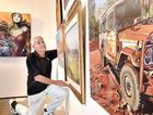 "IMPRESSION: Hervey Bay Art Gallery - 32nd Hervey Bay Art Society annual exhibition - president Rolf Sieber helps hang the works. Patrick Phillips ""Abandoned Troopy"" in the foreground."