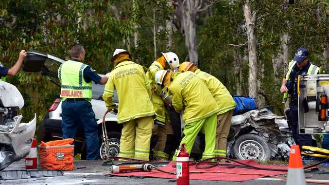 Firefighters work to free a driver trapped in a Sunshine Motorway crash at Peregian Springs.