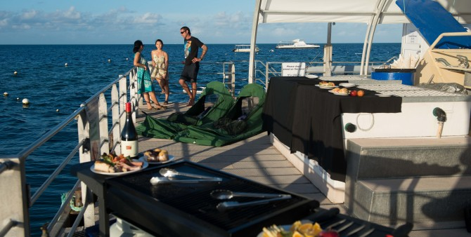 The crew hosts serve up a three-course gourmet barbecue dinner for guests spending the night at Moore Reef Pontoon on the Great Barrier Reef.