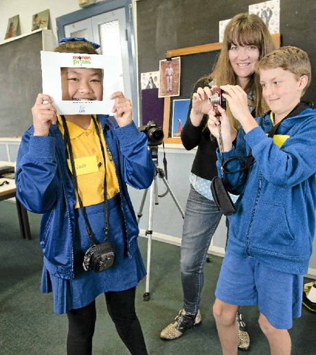 SMILE: Year 5 student Linda Mai poses for fellow student Alex Laughton of Year 6 as he gets tips from photographer Louise Whelan.