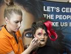 Bree Logan paints Kirsten Rolls' face in the emerging artist exhibit during an industry showcase.