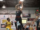 Mackay Meteors guard Tyson Demos goes aerial against the Brisbane Capitals in game two of the finals series with coach Joel Khalu (right) looking on.
