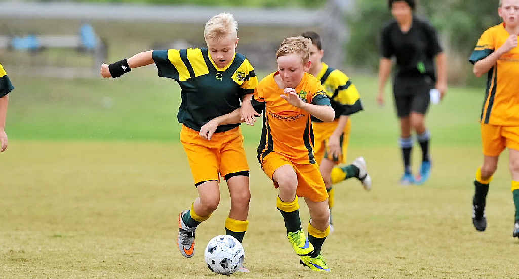 BRING IT ON: Lachlan Allan and Luke Johnston race for the ball while playing at the Terry West Carnival held at Palm Drive fields.