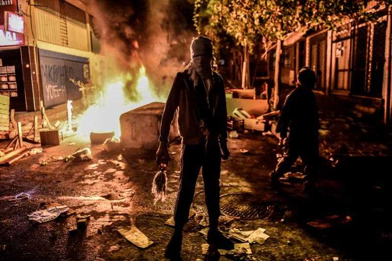 A masked kurdish militant holds a molotov cocktails in front of a burning barricade during clashes with Turkish police on August 27,2015 in the Gazi district of Istanbul. Five people, including two children and a soldier, were killed in clashes between Kurdish militants and security forces in Turkey's restive Kurdish-majority southeast on August 27, 2015, local officials and the army said.