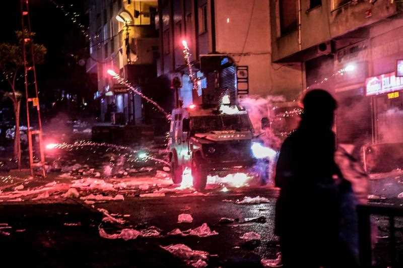 Millitants lobb fireworks towards an armoured police vehicle during clashes with Turkish police, on August 27, 2015 in the Gazi district in Istanbul. Five people, including two children and a soldier, were killed in clashes between Kurdish militants and security forces in Turkey's restive Kurdish-majority southeast on August 27, local officials and the army said.
