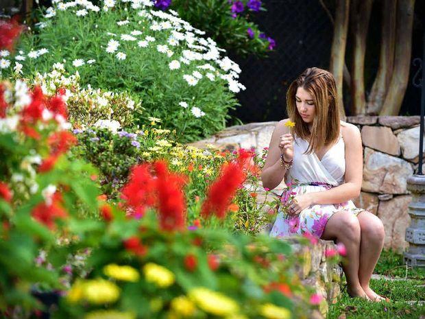 SITTING PRETTY: Deni Barnett, of Coolum, enjoys the warmth of spring in the garden.