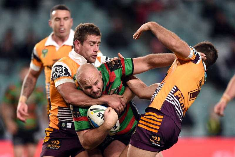 Glenn Stewart (centre) of the Rabbitohs is tackled by Ben Hunt (right) and Andrew McCullough of the Broncos during the round 25 NRL match between the South Sydney Rabbitohs and the Brisbane Broncos at Allianz Stadium in Sydney on Thursday, Aug. 27, 2015.