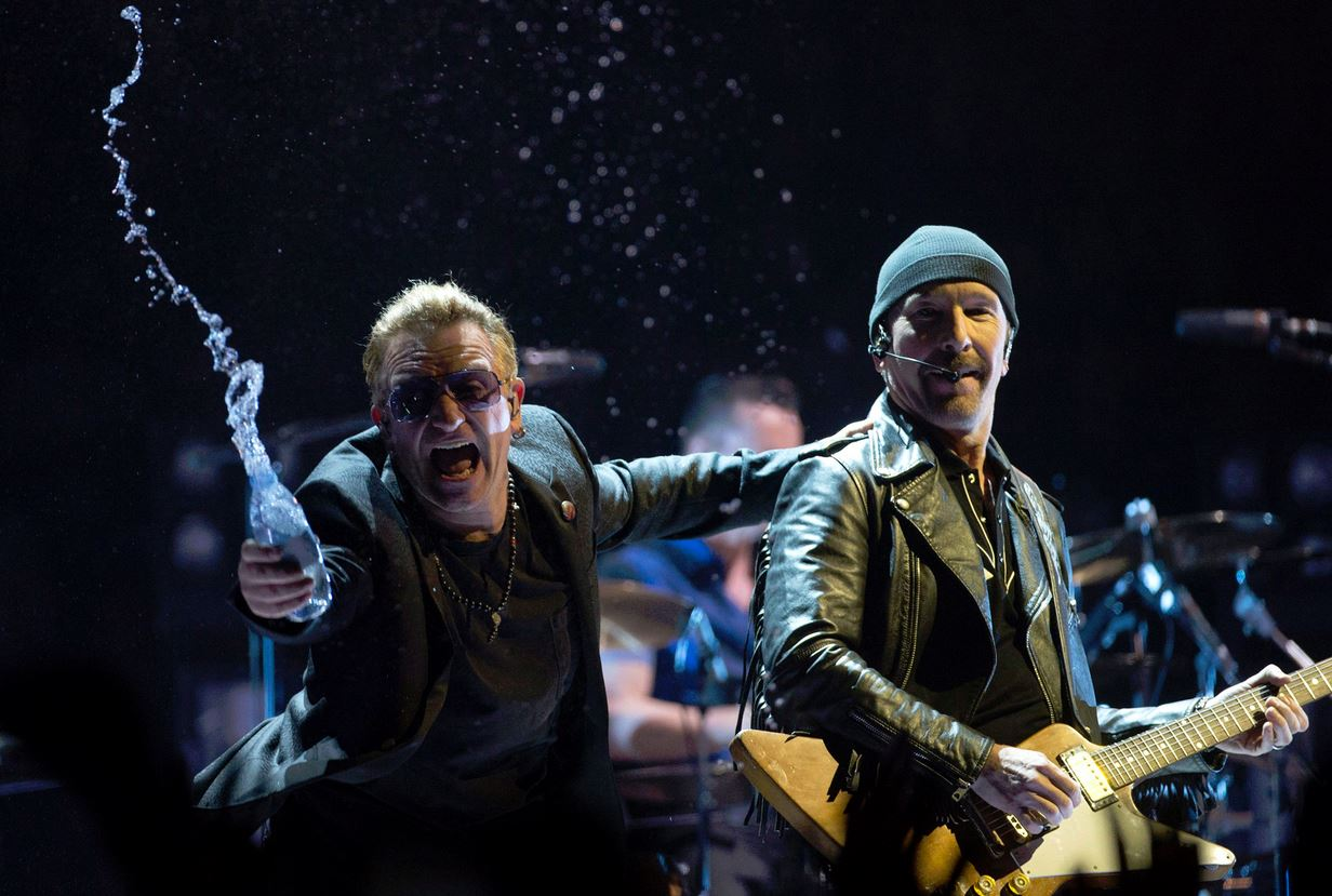 Bono throws water at the crowd while the Edge watches as they perform in the band's first concert of their new world tour in Vancouver