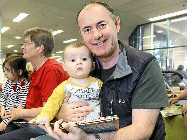 LET'S READ: Jason Gill reads with nine-month-old Adam Jay Bowers at Ipswich Central Library.