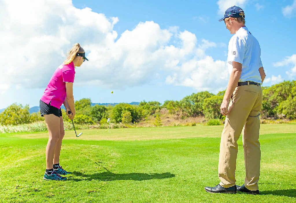 EXTRAORDINARY AWARDEE: Katie Campbell gets some tips from Hamilton Island Golf Club pro Steven Sandilands.