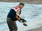A Turkish police officer carries a young boy who drowned in a failed attempt to sail to the Greek island of Kos.