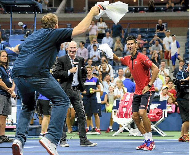 STRUTTING HIS STUFF: Novak Djokovic dances on the court with a fan after defeating Andreas Haider-Maurer of Austria.