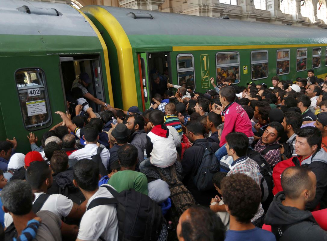 Refugees ruch onto a train at the Keleti station in Budapest, Hungary, after police withdrew from gates on 3 September