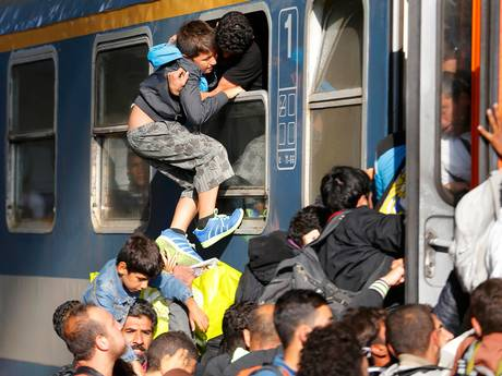 Refugees storm into a train at the Keleti train station as Hungarian police withdrew from the gates after two days of blocking their entry