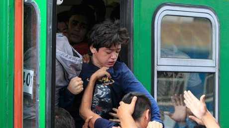 Refugees storm into a train at the Keleti train station in Budapest
