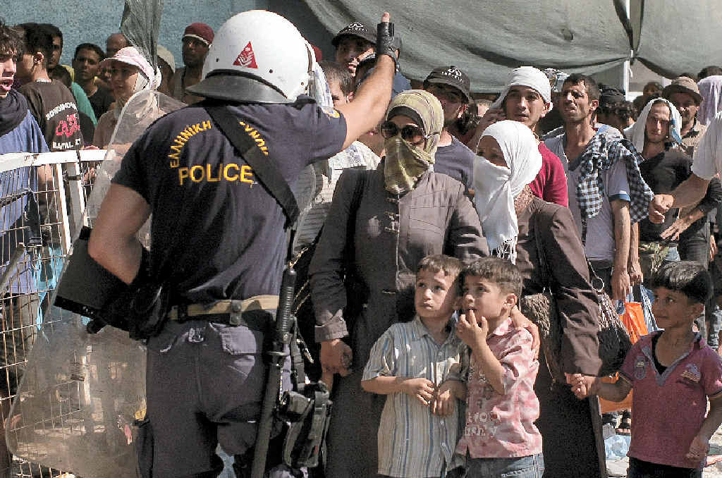 A Greek policeman tries to put migrants and refugees waiting for a registration procedure in a line, at the port of Lesbos, Greece.