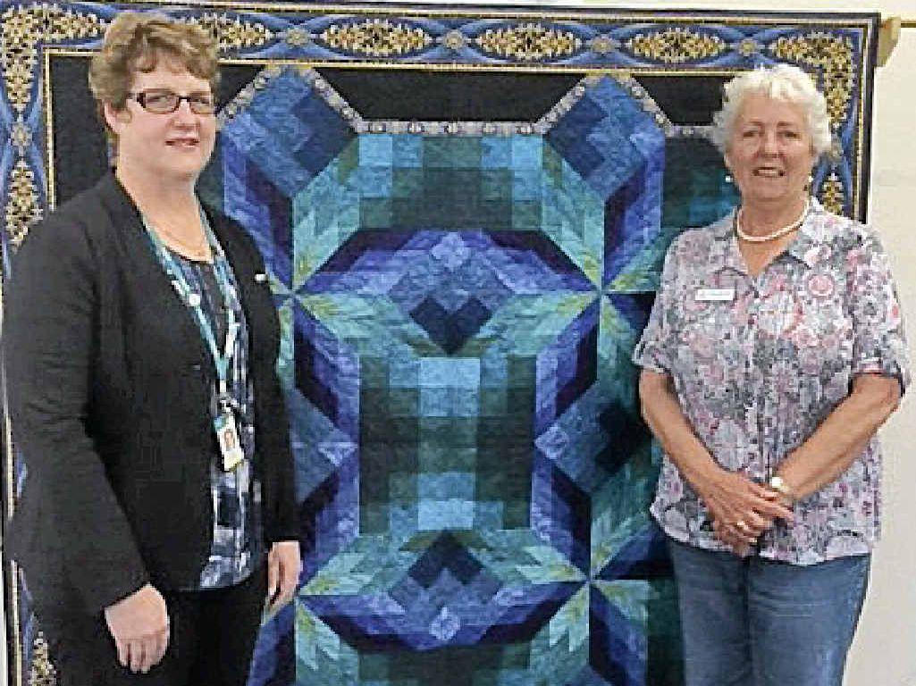 Jayne Swift Manna House co-ordinator and Ineke Schouteten TQ events co-ordinator displaying the 2015 raffle quilt.
