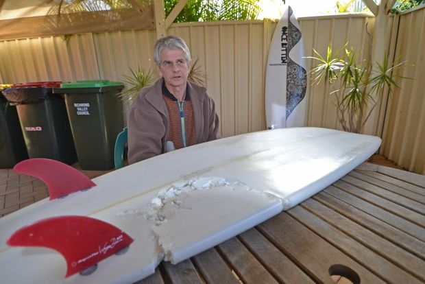 ONCE BITTEN: Evans Head resident Craig Ison with the board he was riding when he was attacked by a great white shark at Main Beach. In the background is the new board made for him by his good friend Darin Reilly.