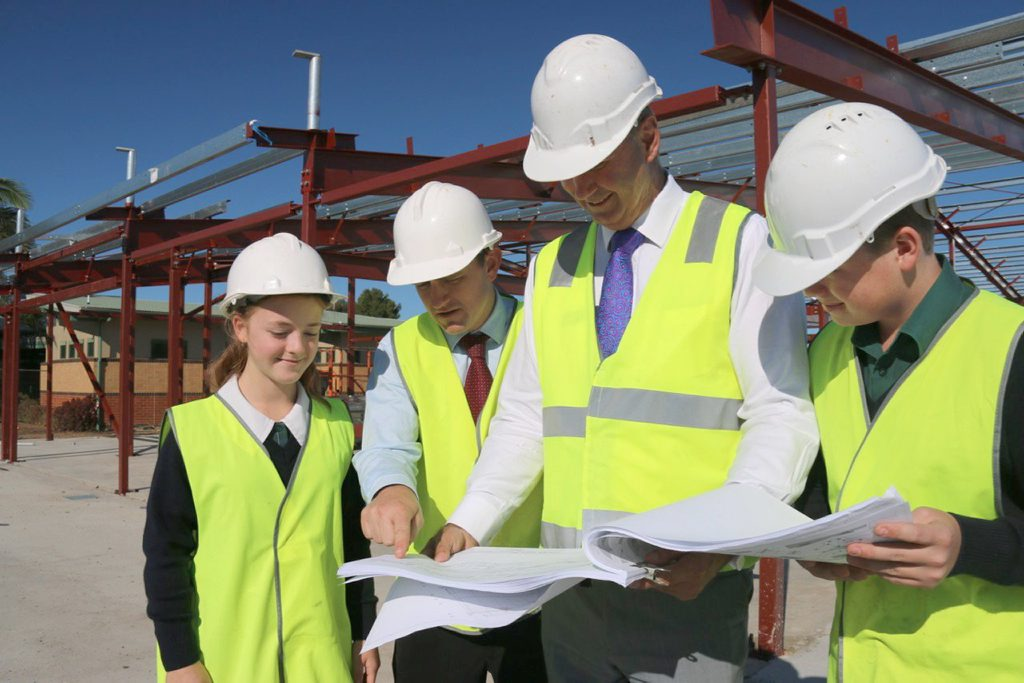 UNDER CONSTRUCTION: Student Jael Sitte, St Lukes Anglican College head of middle school Ryan Collins, principal Martin Oates and student Chase Johnstone, look at the plans for the Middle School building. Photo Contributed