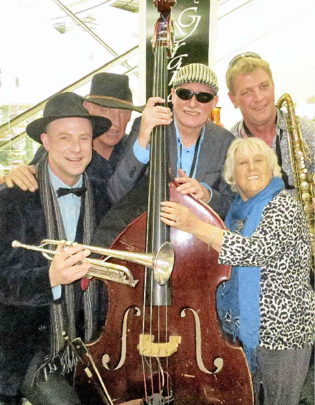 Carmel, a Gold Coast pensioner and jazz enthusiast, is pictured with new and old members of the group at the jazz festival – Mal Wood (trumpet), John Conley (double bass and bass guitar), Willy Qua (saxophone, flute and drums), and Richard Booth (sax, clarinet, trombone and steel drums).