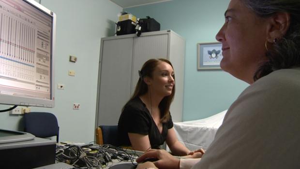 Audiologist Lisa Goode sets a program for Jennifer's cochlear implant.