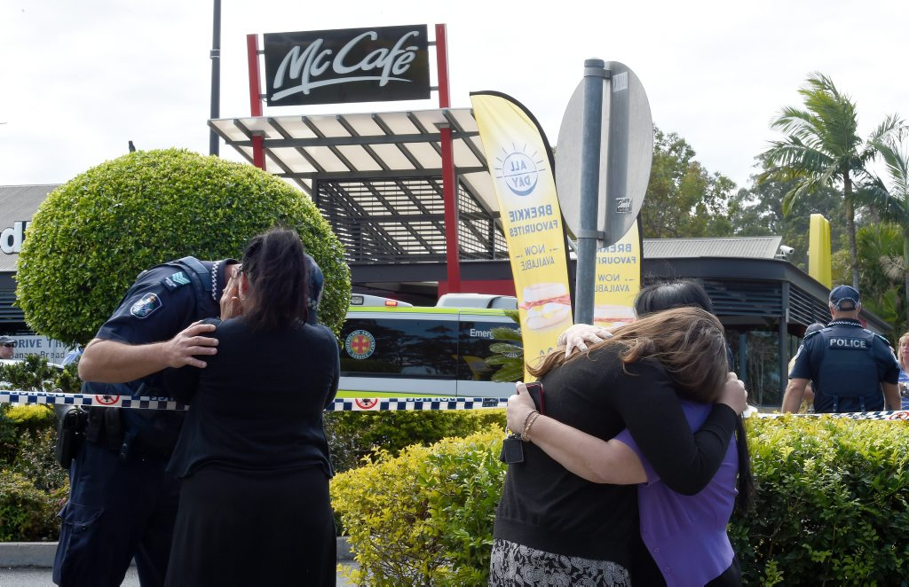 People react following a shooting at a McDonalds restaurant in Helensvale on the Gold Coast.