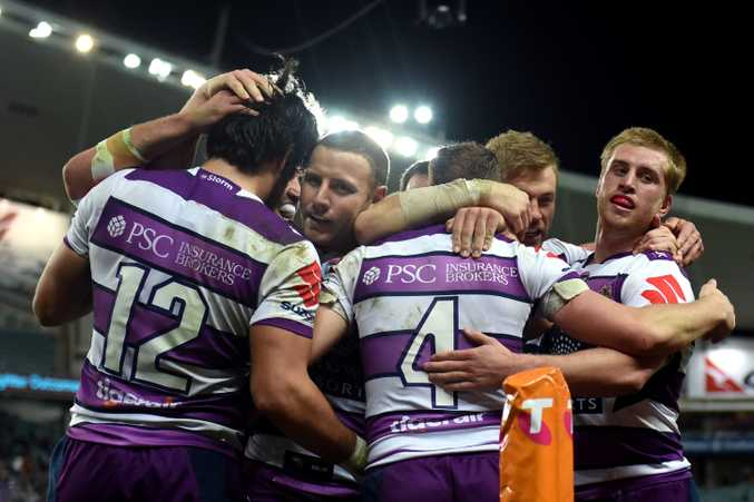 Kurt Mann (centre) of the Storm is congratulated after scoring a try against the Roosters during the first NRL Qualifying Final. (AAP Image/Paul Miller)