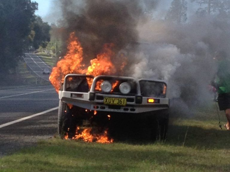 FIREBALL: Flames engulf a four wheel drive on the Casino Rd, north of Grafton on Sunday. A Sydney family of three was able to get most of its valuables from the car safely before it burst into flames.