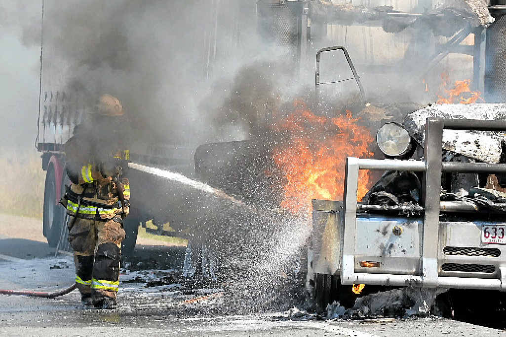 CHARRED SHELL: A firefighter douses a burnt-out truck on the Frizzo Rd exit of the Bruce Hwy at Palmview yesterday.