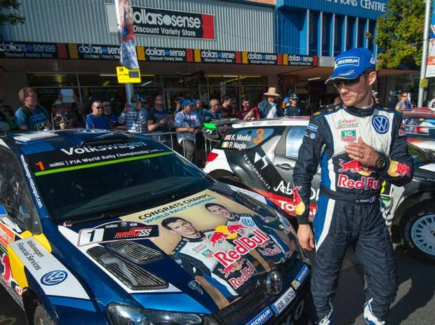 CHAMPION: WRC Rally world champion Sebastien Ogier admires his new-look bonnet last Sunday in the Coffs Harbour after retaining his WRC title.