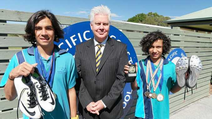 Junior running stars Kytelan Neveceral, 16, (left) and Tynan Neveceral, 11, (right) display their medals and gear with a proud Pacific Coast Christian College principal Patrick Donnelly.