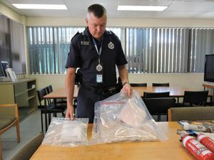Acting Senior Sergeant Chris Farlow inspects the ecstasy pills found in a speeding driver's car.