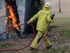 Fireman putting out Small fire on a tree located in a park. Photo Kate Reynolds / The Morning Bulletin