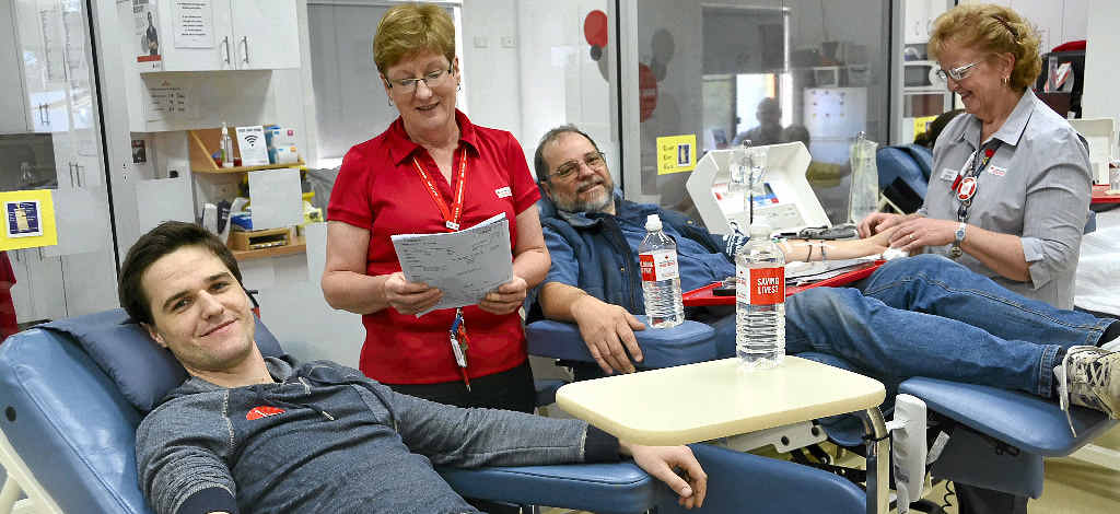 GIFT OF GIVING: Regular blood donor Barry Anderson (right) shows his son Ben how it's done with the help of registered nurse Mary Jones.